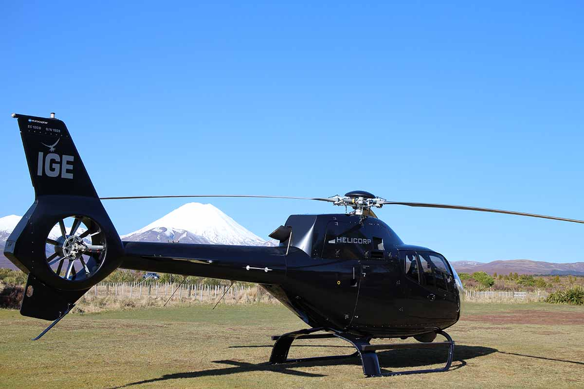 Helicorp ZK-IGE with snow-capped Mt Ngauruhoe in the background parked at Discovery helipad