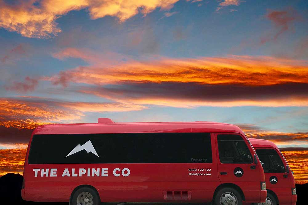 The Apline Co's early Tongariro Crossing shuttle buses owned and operated by Discovery Lodge with beautiful sunrise