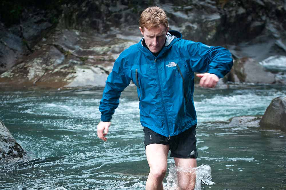 Callum Harland, owner of Discovery Lodge crossing a mountain stream in the Tongariro National Park
