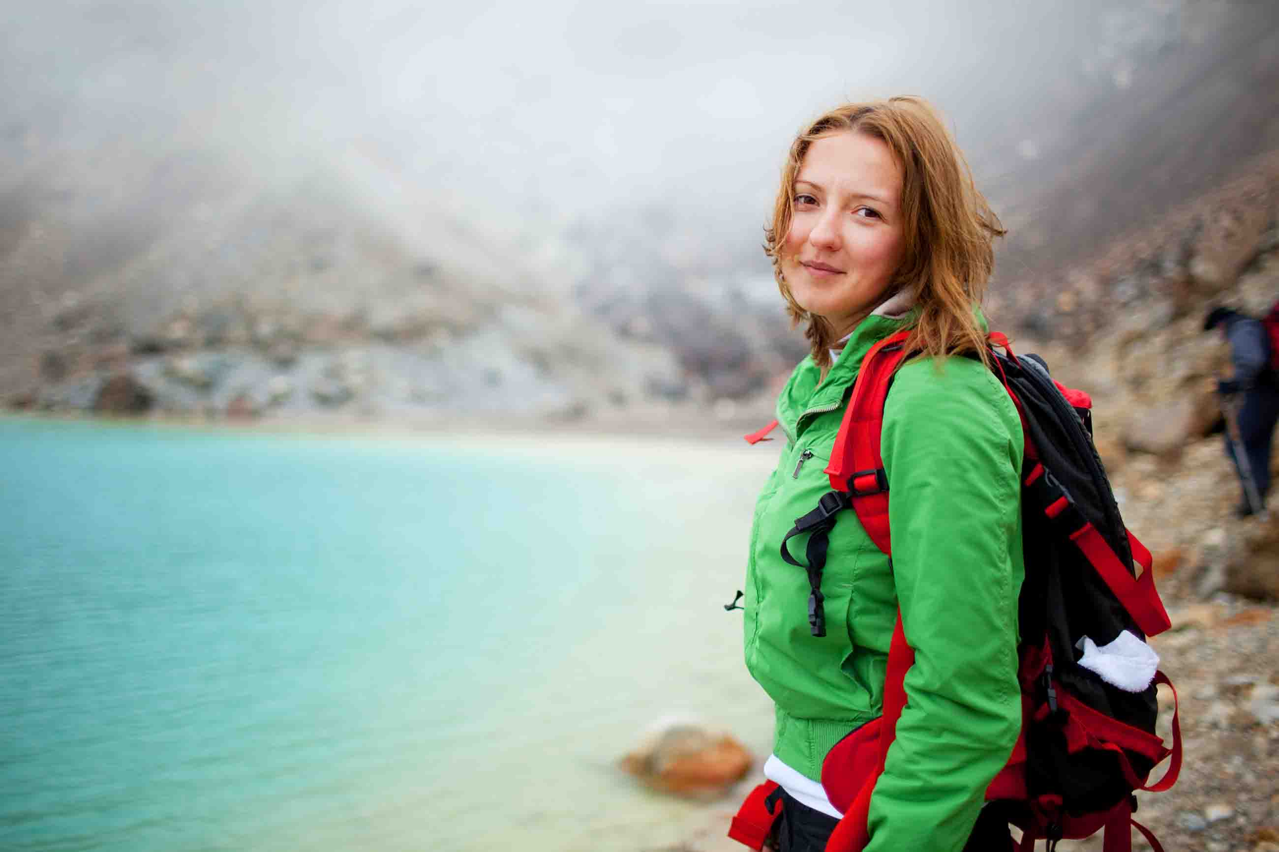 A young female standing next to the Emerald Lakes on the Tongariro Alpine Crossing