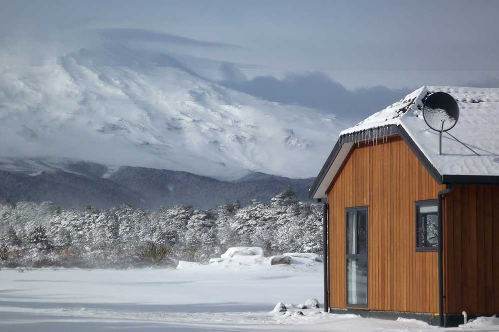 A Discovery Lodge chalet surrounded by snow with Whakapapa Mt Ruapehu in the background