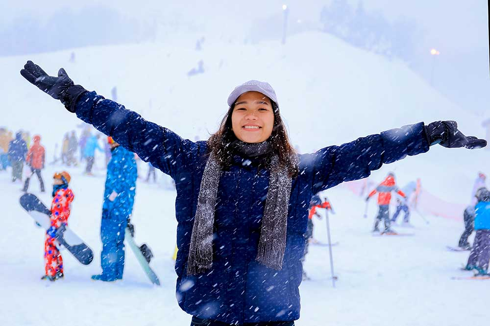 A young lady having fun in the snow with snow boarders and skiers in the background