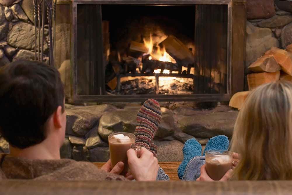A couple enjoying hot chocolates at a cafe bar next to an open fire