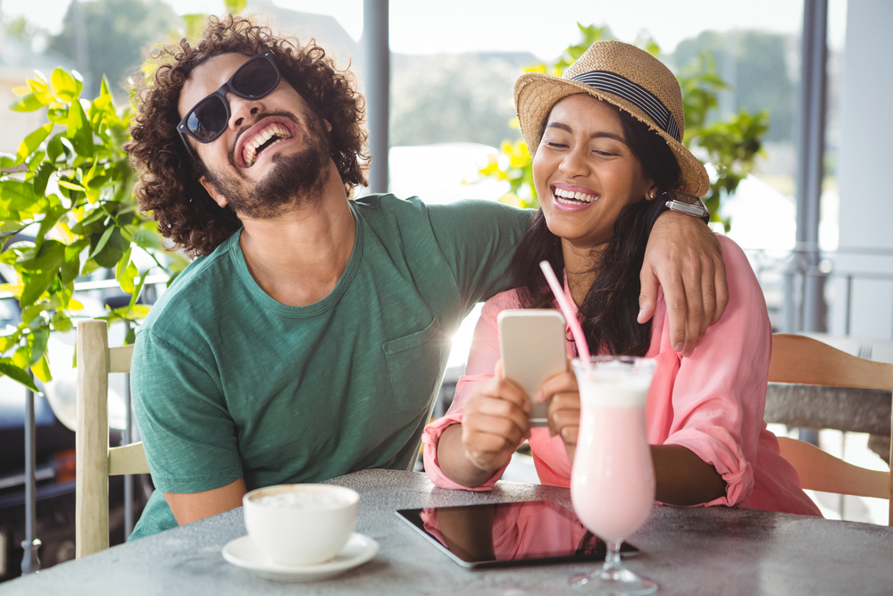 A couple laughing and enjoying a coffee and smoothy at a cafe close to Discovery Lodge Tongariro