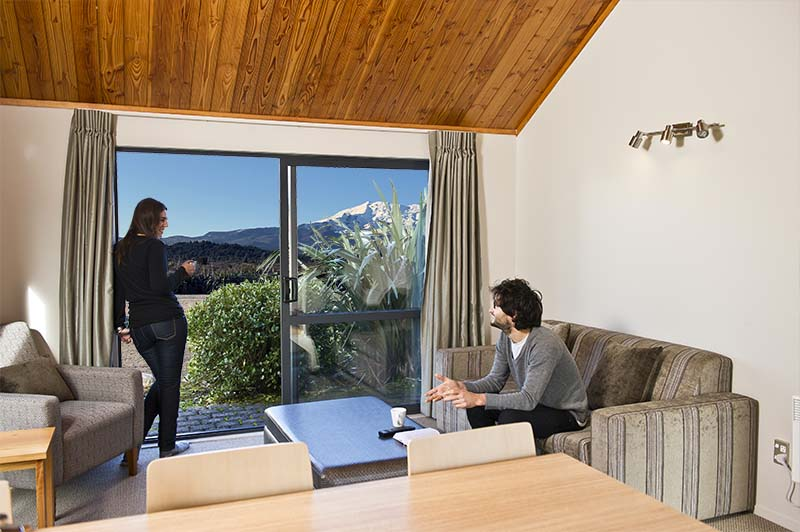 Two guests inside a Discovery Lodge chalet one bedroom at Tongariro National Park with views of Mt Ruapehu