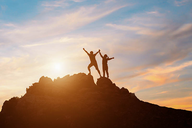Two people standing on a rocky outcrop with their arms raised in triumph while watching the sun rise