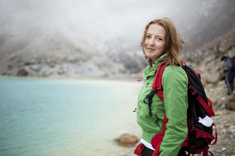 A women standing next to the Emerald Lake on the Tongariro Crossing