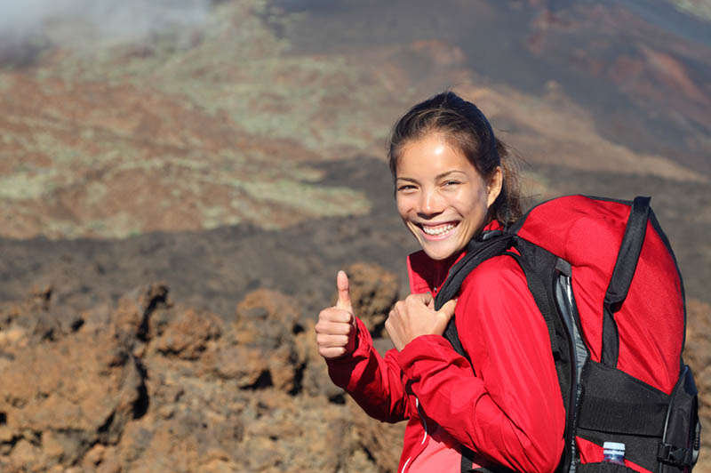 A women giving thumbs up with volcanic rock in the background