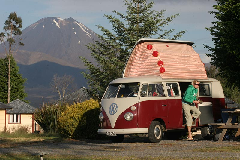A classic VW camper van at a Discovery Lodge camper site surrounded by trees with Mt Ngauruhoe in the background