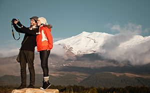 Couple taking selfie from Discovery Lodge Tongariro with Mt Ruapehu in background