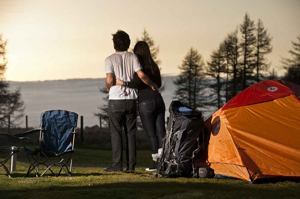Two campers with their arms around each other next to a marmot tent watching the sun set from Discovery Lodge Tongariro