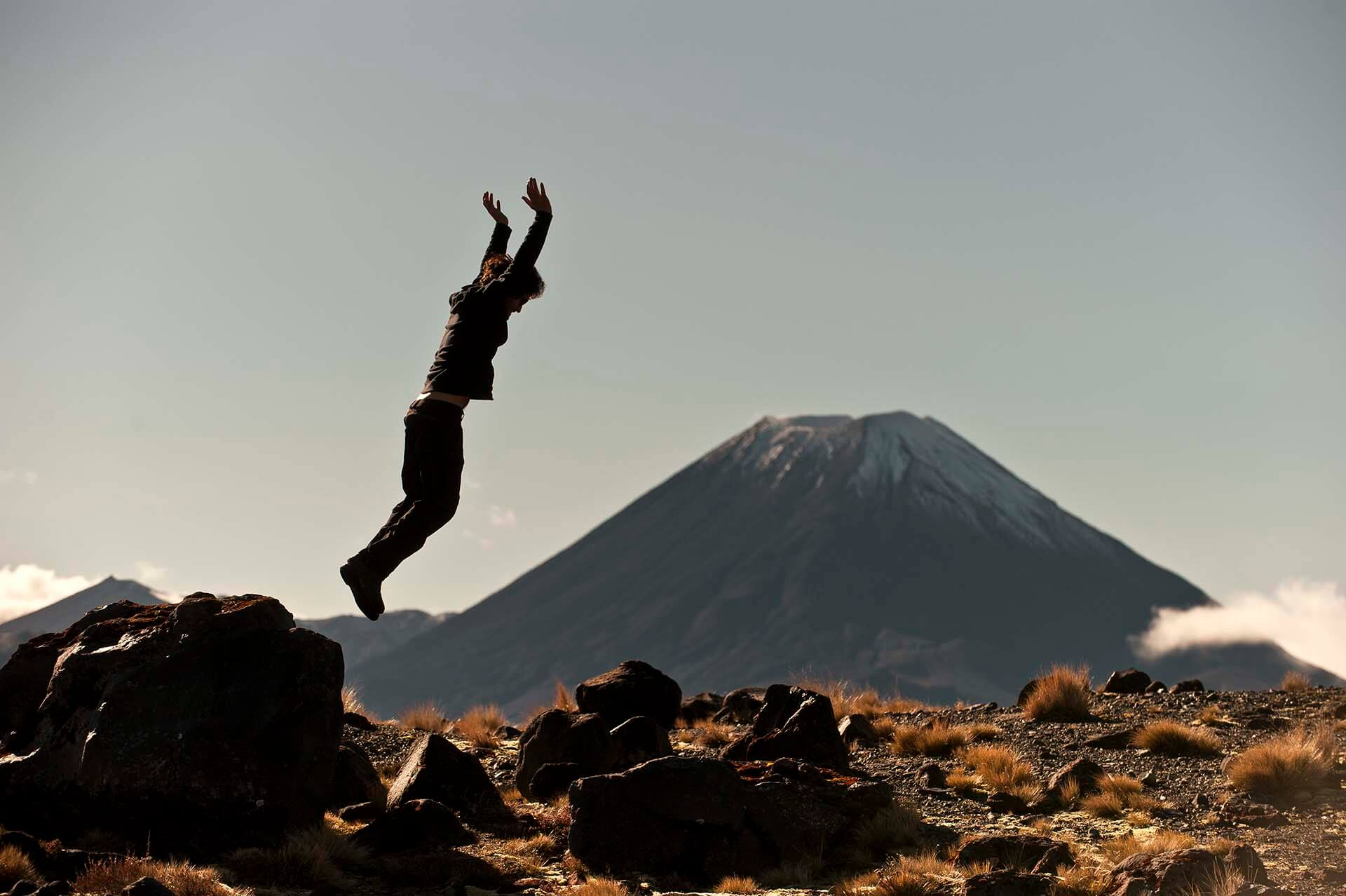 A happy Discovery Lodge guest jumping off a rock with Mt Ngauruhoe