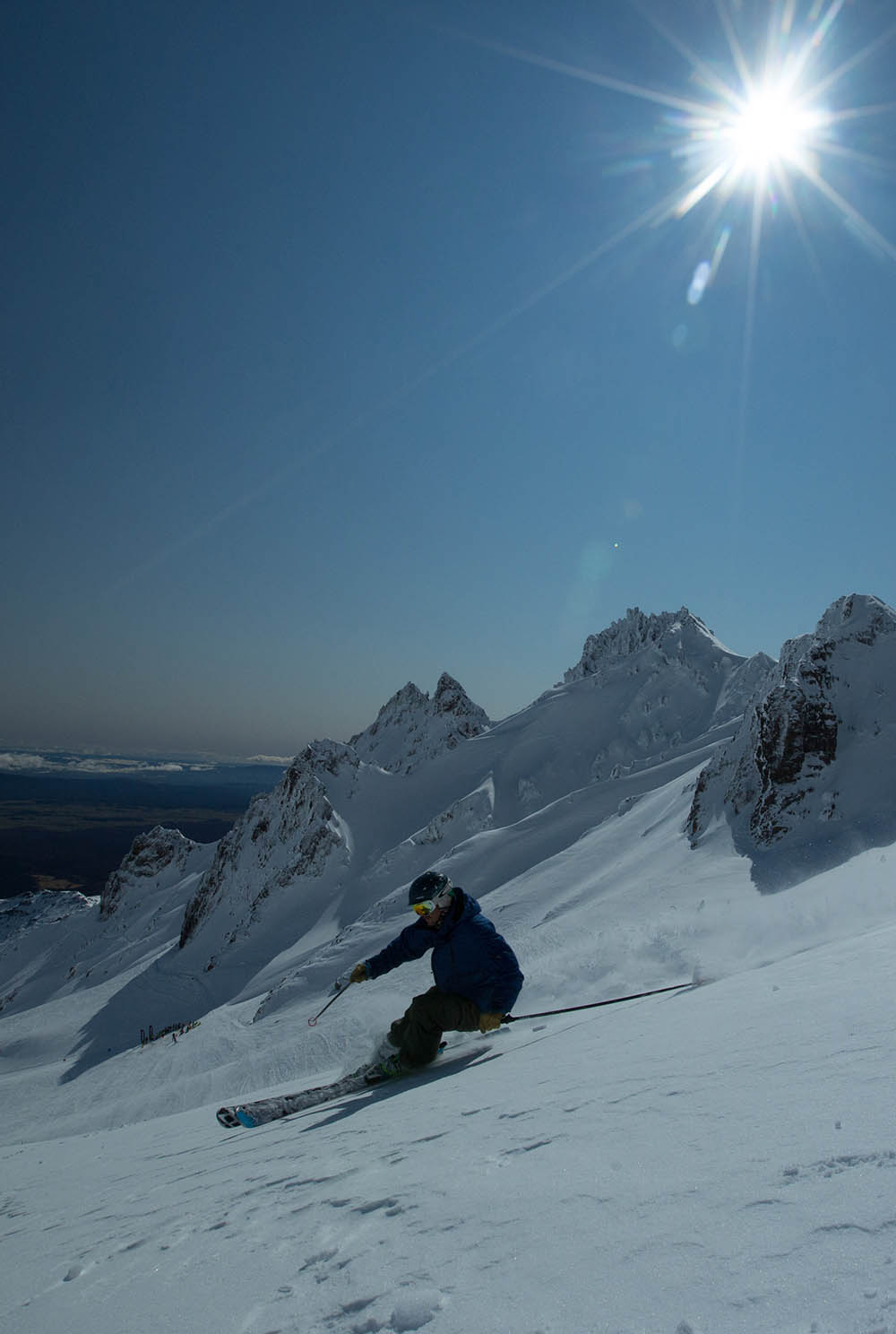 A skier skiing with the Pinnacles of Whakapapa Mt Ruapehu in the background