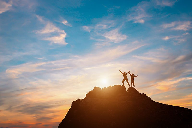 Silhouette of two hikers with arms raised standing on a rocky peak