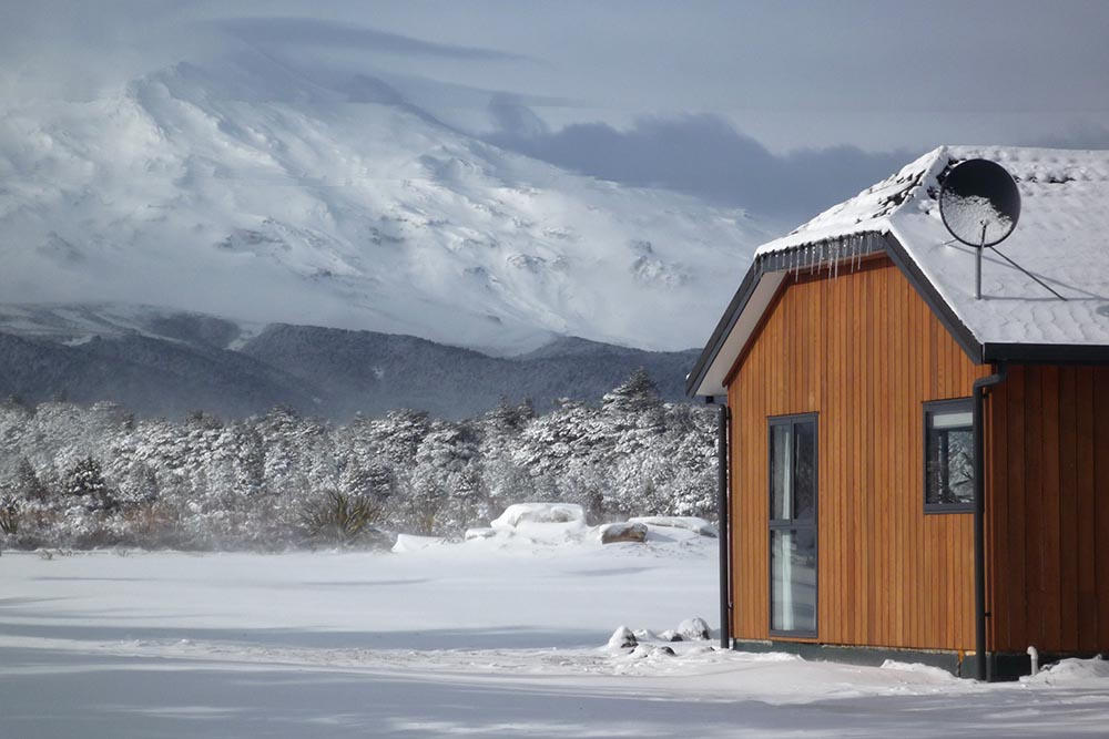 Discovery Chalet amongst snow with Mt Ruapehu