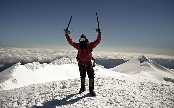 Man at top of mountain surrounded by snow
