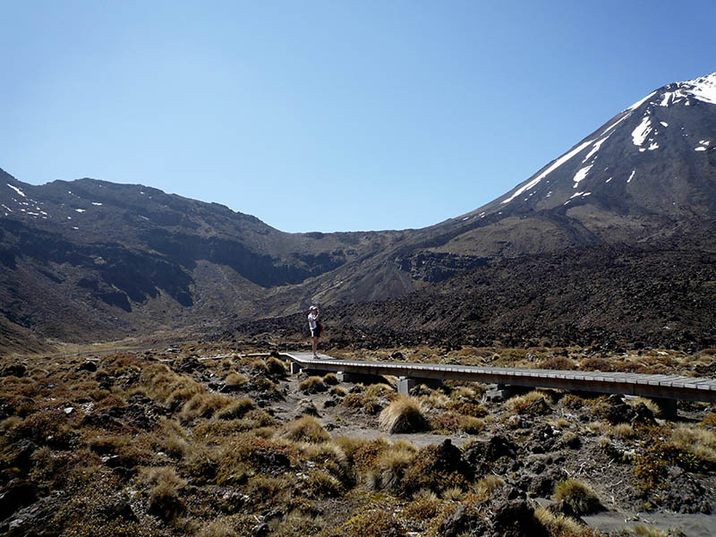 A hiker standing on board walk in the Mangatepopo Valley taking a photo of Mt Ngauruhoe