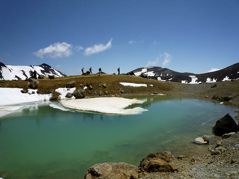 The Emerald Lakes with a little snow and hikers walking the Tongariro Alpine Crossing