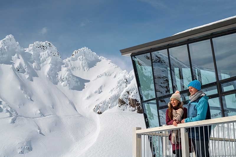 Two people standing outside the Knoll Ridge Cafe with the Pinnacles of Mt Ruapehu in the background at Whakapapa