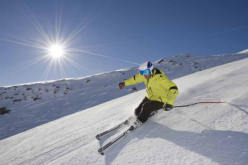 Skier with sunshine and blue ski